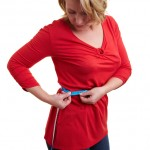 woman with red top and tape measure around waist